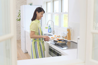 明るいキッチンで料理をする日本人女性