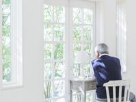 窓辺から遠くを見るシニア日本人男性