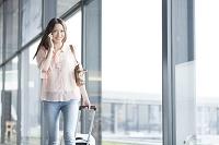 空港で電話する日本人女性