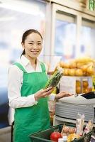 レジで会計をする日本人女性店員