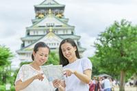 大阪城と地図を見る日本人女性