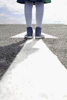 道路の矢印の上に立つ若い女性