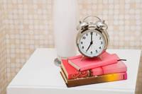 目覚まし時計と本が置かれたナイトテーブル