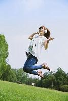 原っぱでジャンプする日本人女性