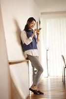 壁にもたれて携帯を持つ日本人女性