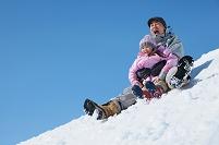 ゲレンデを滑り降りる日本人親子