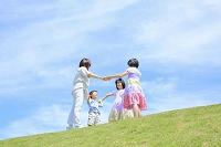 土手で手を繋ぐ母親と子供