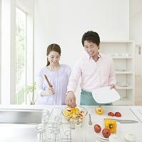 キッチンでサラダを盛り付ける夫婦