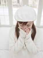 うつむいて口に手を当てる日本人女性