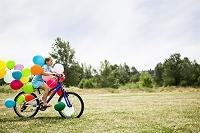 風船をつけた自転車に乗る女の子