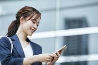スマートフォンを見る日本人ビジネスウーマン
