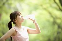 ペットボトルの水を飲む日本人女性