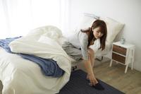 ベッドから起き上がる日本人女性