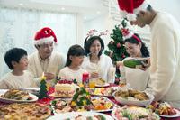 クリスマスディナーを前にシャンパンを注ぐ父親