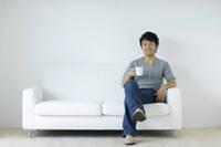 リビングのソファーで寛ぐ男性