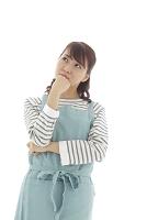 悩むエプロン姿の若い日本人女性