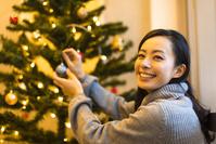 クリスマスツリーの飾り付けをする日本人女性