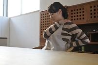 キッチンで凝った肩に手をあてる日本人女性