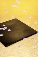 金の紙の上の黒の漆の盆の上に落下している桜の花びら