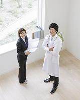 窓辺に立つビジネス女性と医師
