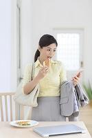出勤前にスマートフォンを見ながら朝食を食べる女性