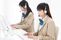 インカムをつけてパソコンをする女子高校生