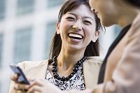 友人にスマートフォンを見せる若い日本人女性