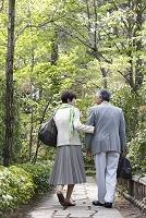 旅行カバンを持って歩くシニア夫婦