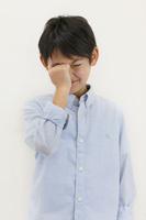 アレルギーで目をこする小学生