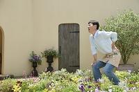 腰痛で腰を押さえる中年日本人男性