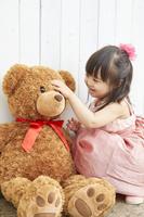 クマのぬいぐるみで遊ぶ日本人の女の子