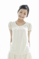 微笑みながら少しうつむく若い日本人女性