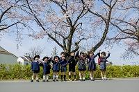 桜の咲く道で手を繋ぐ新一年生と新入園児