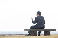 ベンチに座ってスマホを見るビジネスマン