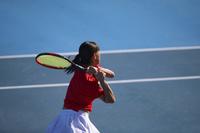 バックハンドをする女子テニス選手