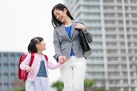 手を繋いで歩く女の子と母親