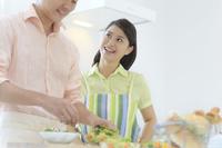 料理をする夫と見守る妻