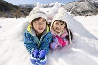 雪山でカマクラに入る日本人の子供