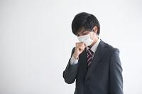 マスクをして咳き込むビジネスマン