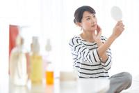 鏡を見て頬に手をあてる日本人女性