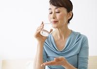 サプリメントを飲むシニアの女性