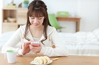 部屋でスマートフォンを見る日本人女性