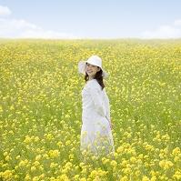 菜の花畑で振り返る笑顔の日本人女性