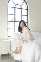 大きな窓のある広い寝室のベッドで目覚めた日本人女性