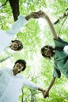 手を繋いで輪になる若者たちと緑の木々