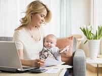 赤ちゃんを抱きながら仕事する女性
