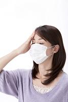 発熱で頭に手をやるマスクをした女性