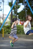 ブランコで遊ぶ日本人親子