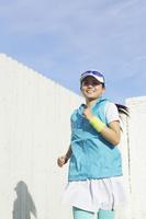 青空の下でランニングする日本人女性