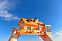 模型の家を持つ手と青空
